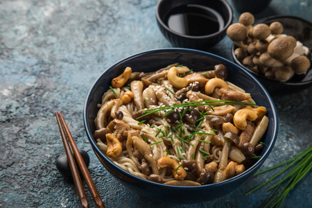 noodles with chicken and shimeji mushrooms in blue  bowl, selective focus