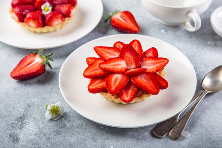 tart with fresh strawberry on white plate , selective focus
