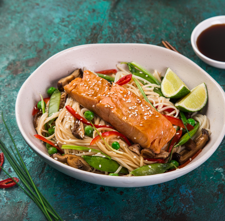 salmon with noodles and vegetables in asian style , selective focus, square image