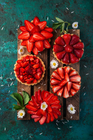 strawberry tartlets  on green background, top view