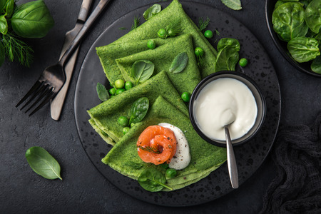 spinach crepes with smoked salmon and yogurt sauce on black plate, dark background, top view