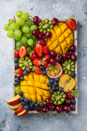 delicious fruits and berries platter.  Mango, kiwi, strawberry, grape, cherry, blueberry, peach and passion fruit on white wooden tray, top view