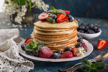 pancakes served with fresh berries, dark background