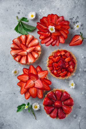 strawberry tarts on gray background, top view, copy space