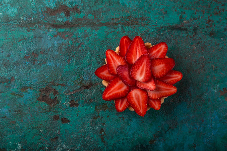 strawberry tartlet  on green background, top view, copy space