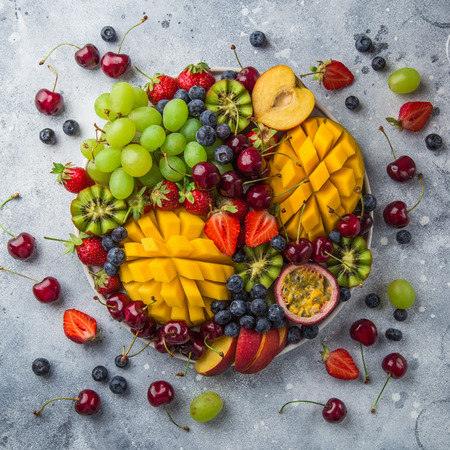 delicious fruits and berries platter.  Mango, kiwi, strawberry, grape, cherry, blueberry, peach and passion fruit, top view, square image Stockfoto