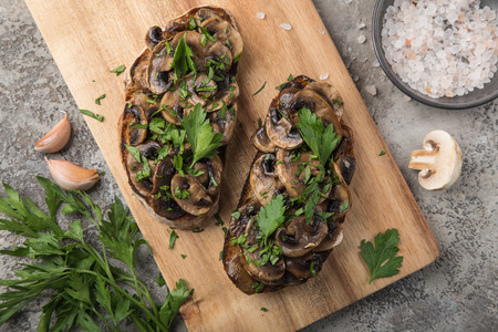 mushrooms garlic toasts on wooden cutting board, top view