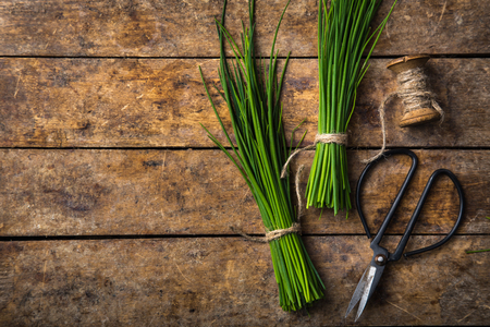 fresh chives on wooden rustic background, top view, copy space