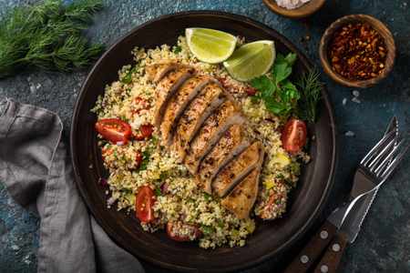 grilled chicken breast with vegetable couscous salad, top view, dark blue background