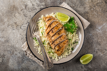 Grilled chicken breast with herb couscous, top view, square image