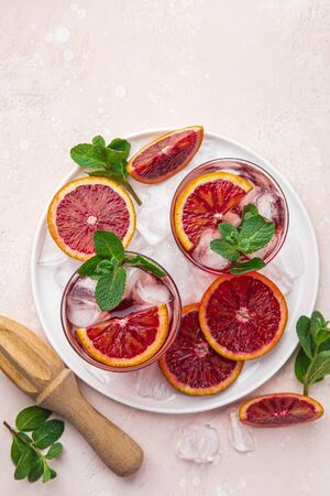 red blood orange cocktail with ice and fresh mint, top view, pink  background 版權商用圖片