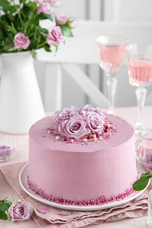 festive pink cake on white cake stand decorated with fresh roses for Valentines Day, selective focus Фото со стока