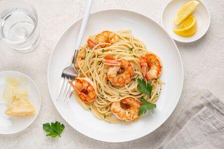 lemon and garlic shrims spaghetti pasta on white plate, top view