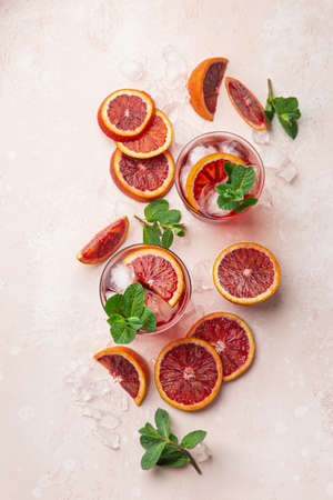 red blood orange cocktail with ice and fresh mint, top view, pink  background Stok Fotoğraf