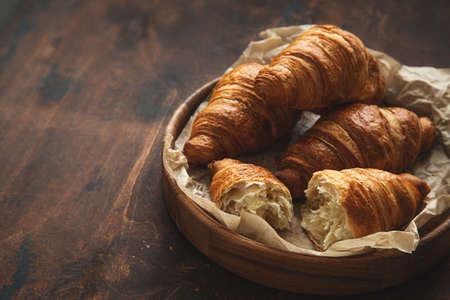 Freshly baked croissants, dark wooden background, selective focus, toned, copy space Stock Photo