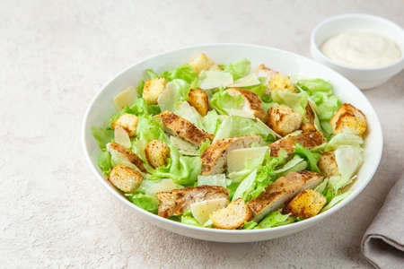 traditional Caesar salad with lettuce, roasted chicken, croutons and cheese in white bowl, selective focus. copy space