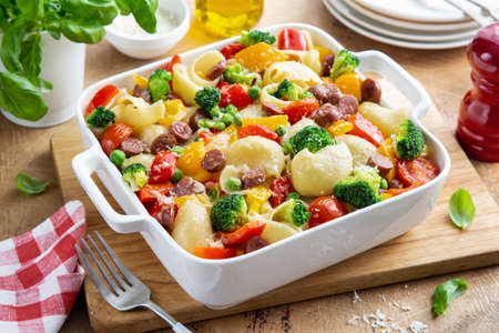 baked vegetable and sausages lumaconi pasta in white baking dish, wooden background, selective focus