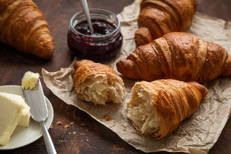 Freshly baked croissants with berries jam and butter, dark wooden background, selective focus Archivio Fotografico