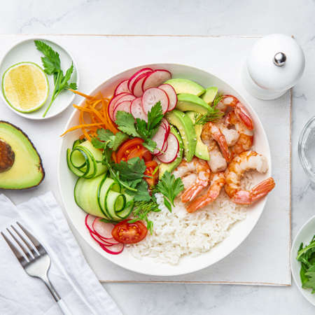 Avocado, prawn, cucumber, tomato, radish, carrot and rice salad bowl. Healthy food. White background, top view, square image 스톡 콘텐츠