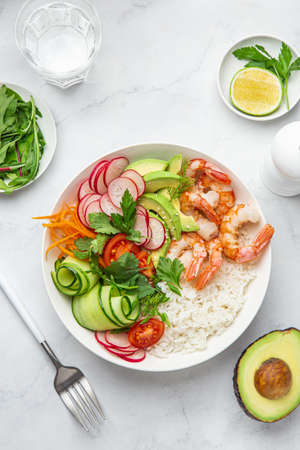 Avocado, prawn, cucumber, tomato, radish, carrot and rice salad bowl. Healthy food. White background, top view