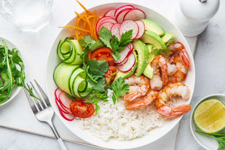 Avocado, shrimps, cucumber, tomato, radish, carrot and rice salad bowl. Healthy food. White background, top view 스톡 콘텐츠