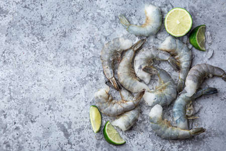 Fresh raw peeled prawns on ice, gray concrete backgrond, top view, copy space