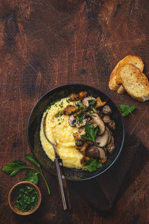 Creamy polenta with fried mushrooms, wooden background, top view, copy space Stok Fotoğraf