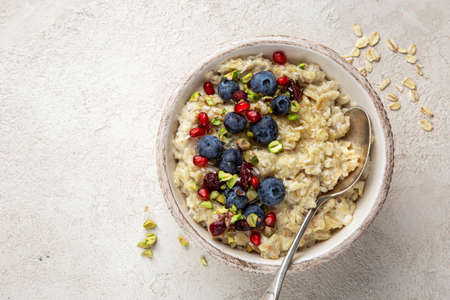 Oatmeal porridge with fresh berry, nuts and honey in bowl, copy space Stok Fotoğraf
