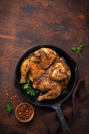 whole fried chicken tabaka on cast iron pan, old wooden background. top view. copy space