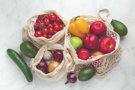 Zero waste and eco-friendly concept. Fresh organic fruits and vegetables in reusable textile shopping bags. top view, toned