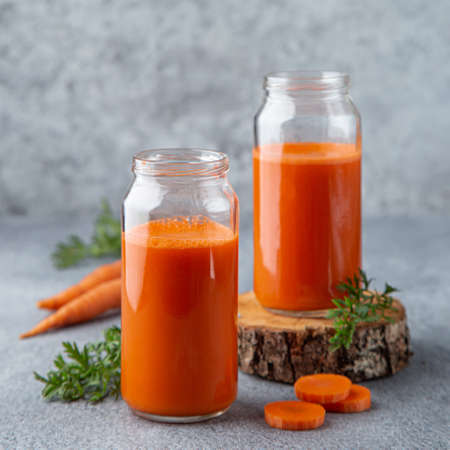 fresh carrot juice, gray background, square image