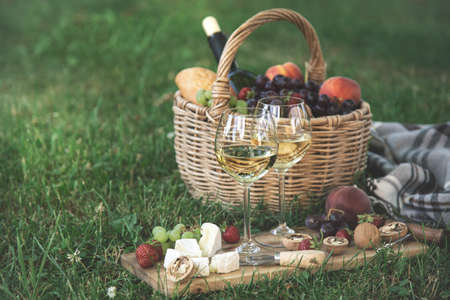 Two glasses of white wine, cheese, fruits. Picnic, outdoor dinner on a green lawn, selective focus, copy space, toned
