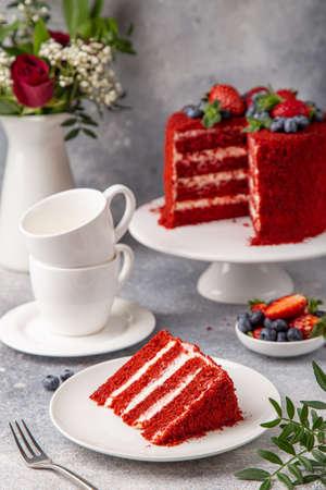 slice of Red Velvet cake on white plate, gray background, selective focus