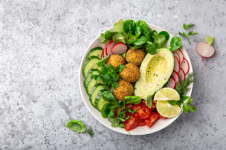 healthy vegan lunch bowl salad with avocado, falafel, cucumber, tomato and redish, top view, copy space