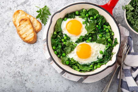 fried eggs with kale, spinach and green peas for breakfast, top view, copy space Banco de Imagens