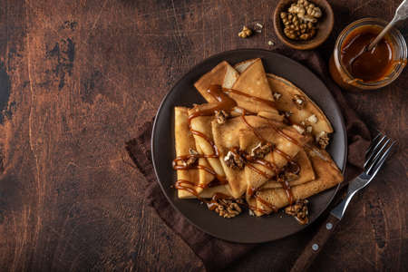 crepes with salted caramel and nuts, top view, wooden background, copy space