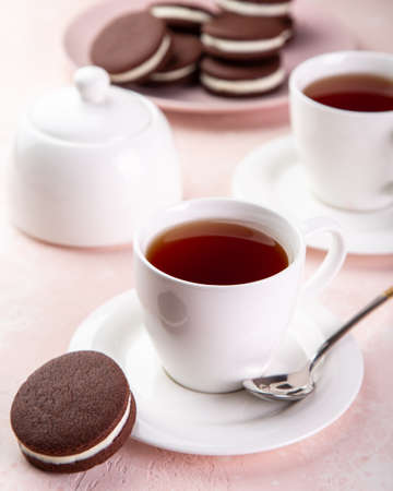 cup of tea and homemade chocolate sandwich cookies, selective focus, pink background,