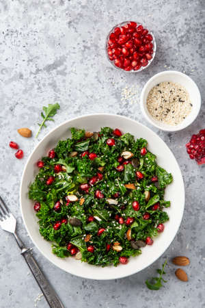 fresh kale, roasted chickpeas, almond and pomegranate salad in white bowl, healthy vegan food, top view, gray background Banco de Imagens