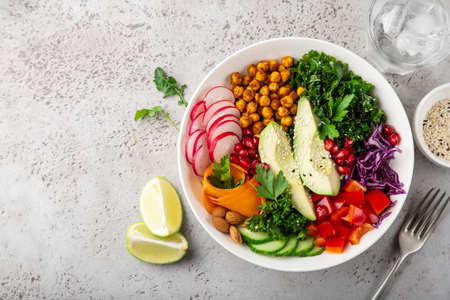 lunch bowl salad with avocado, roasted chickpeas, kale, cucumber, carrot, red cabbage, bell pepper and redish, healthy vegan food, top view, copy space Banco de Imagens