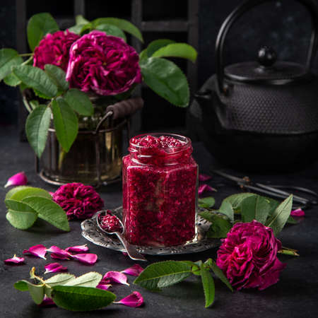 delicious homemade rose jam in jar with rose flowers on dark background ,, square image