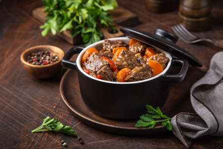 beef stew with vegetables in black pot on dark wooden background, selective focus