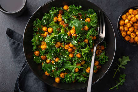 vegan kale and roasted chickpeas salad in black bowl, top view, dark background Banco de Imagens