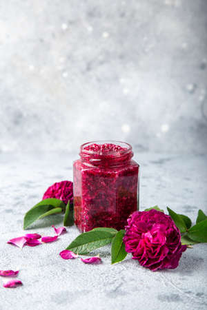 homemade rose jam on glass jar with rose flowers on gray background,