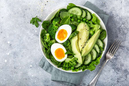 healthy green salad with avocado, eeg, broccoli, cucumber, green peas and spinach in white bowl, top view Banco de Imagens