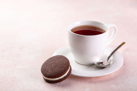 cup of tea and homemade chocolate sandwich cookies, selective focus, pink background, copy space