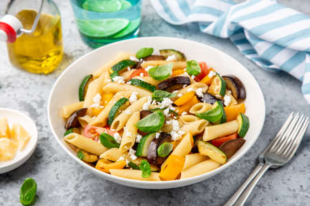 pasta salad with grilled vegetables (zucchini, eggplant, bell pepper ant tomato) and feta cheese on white bowl, selective focus