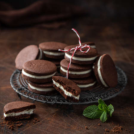 homemade chocolate sanwich cookies with cream cheese filling, selective focus, wooden background, square image Banco de Imagens