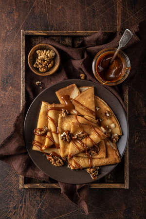 crepes with salted caramel and nuts, top view, wooden background