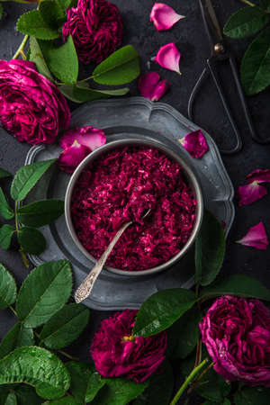 homemade rose jam with rose flowers on dark background, top view Banco de Imagens