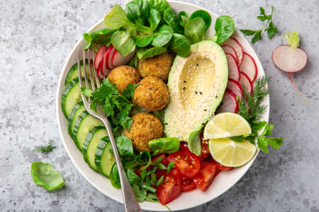 healthy vegan lunch bowl salad with avocado, falafel, cucumber, tomato and redish, top view, square image Banco de Imagens